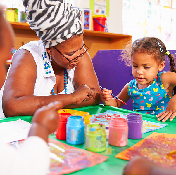 Preschool teacher teaching basic skills such as colors and shapes to little girl